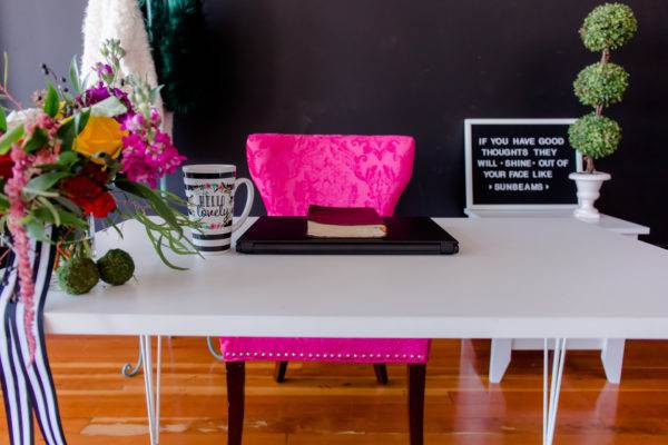 Pink chair with bible on laptop and desk.