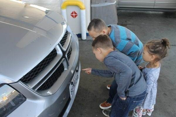 The kids inspecting the bugs on the front of our car during our road trip