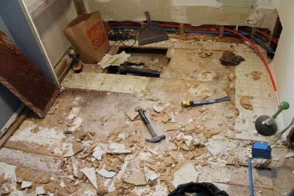 removing old peel and stick tiles in our DIY bathroom remodel