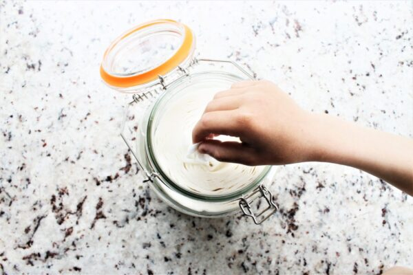 Pulling cleaning wipes out of glass jar