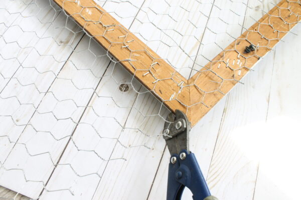 cutting extra chicken wire from picture frame